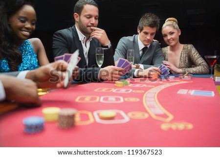 Happy people playing poker in casino