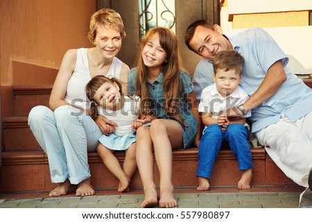 happy playful family on the porch of his house. parents with children in the summer. Mom, dad and kids