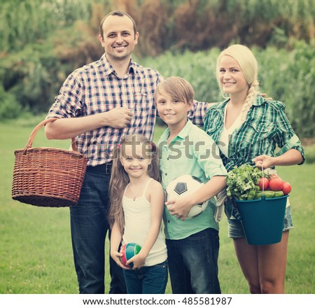 Happy positive family of four spending summer weekend at countryside