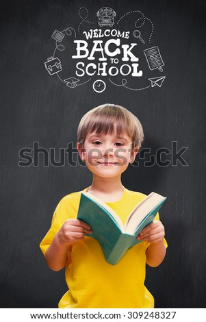 happy pupil with book against blackboard