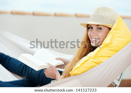 Happy relaxed young woman reading book in the hammock