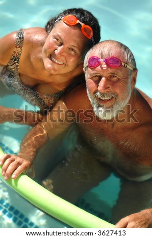 Happy retired couple having fun in the swimming pool in bright matching goggles