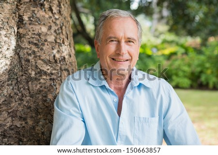 Happy retired man sitting on tree trunk in the park looking at camera