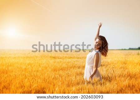 Happy, satisfied young woman with arms outstretched standing in the wheat field.Copy space, sunset, flare light, summer season