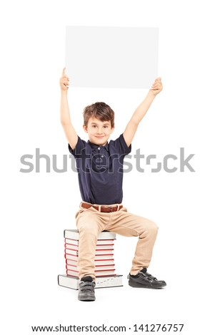 Happy school boy holding a blank panel above his head, seated on a pile of books isolated on white background