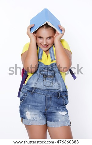 Happy school child smiling and hold books isolated on white. Funny little girl 10 years old with schoolbook. Pupil kid with big backpack at studio.