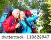 Happy senior couple hiking in the park. - stock photo