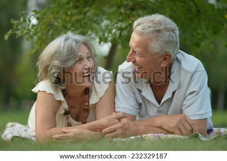Happy senior couple lying in summer park