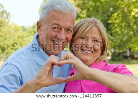 Happy senior couple showing heart symbol on a Valentine`s day