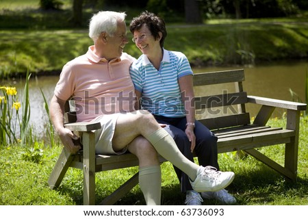 Happy senior couple sitting on a bench