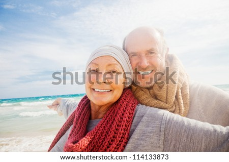 happy senior couple with outstretched arms enjoying retirement flying