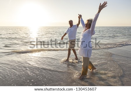 Happy senior man and woman couple dancing and holding hands on a deserted tropical beach at sunrise or sunset