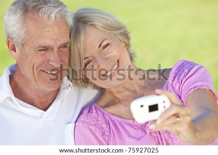 Happy senior man and woman couple sitting together outside in sunshine and taking a self portrait on digital camera