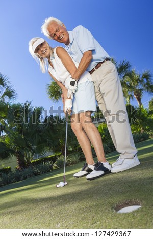 Happy senior man and woman couple together playing golf and putting on a green, the man is teaching the woman how to put.