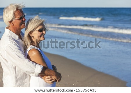 Happy senior man and woman couple together wearing sunglasses & looking out to sea on a deserted tropical beach with bright clear blue sky