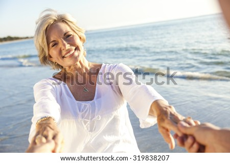 Happy senior man and woman couple walking or dancing and holding hands on a deserted tropical beach