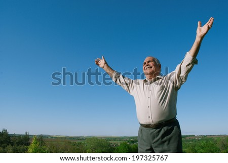 Happy senior man rejoicing in nature standing in open countryside against a sunny blue sky with his arms outspread and a joyful smile, with copyspace