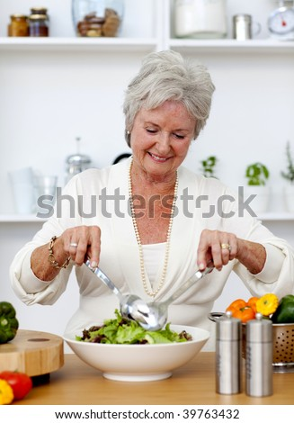 Happy senior woman cooking a salad
