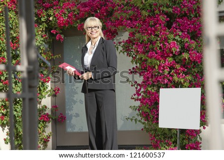 Happy senior woman standing with clipboard