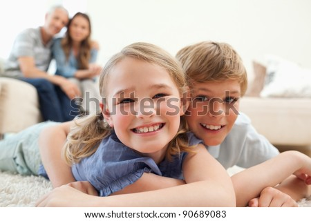 Happy siblings posing on a carpet with their parents on the background in a living room