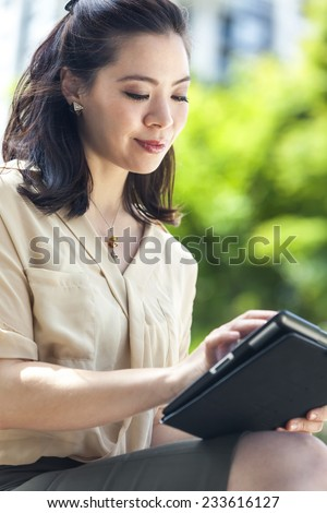 Happy, smiling, beautiful Asian Chinese business woman or businesswoman outside using tablet computer
