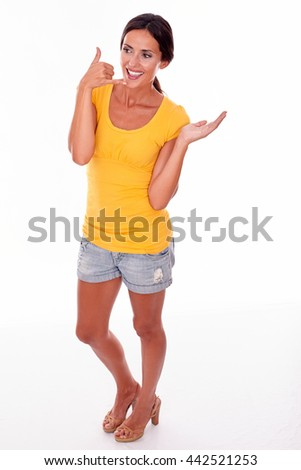 Happy smiling brunette woman gesturing being on the phone while looking away and wearing a yellow t-shirt and short jeans isolated