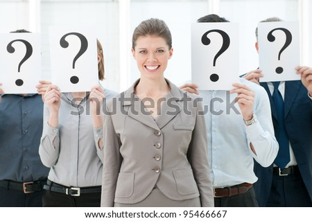 Happy smiling business woman standing out of the crowd with other people hiding their faces behind a question mark sign.
