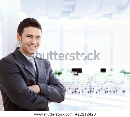 Happy smiling caucasian financial business expert standing at office lobby, arms crossed, looking at camera, copyspace, suit.