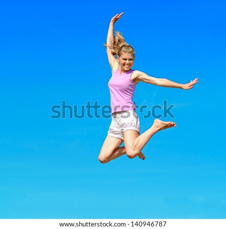 Happy smiling Caucasian woman jumping over sky background.