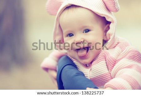 happy smiling cheerful baby girl in pink hood with ears