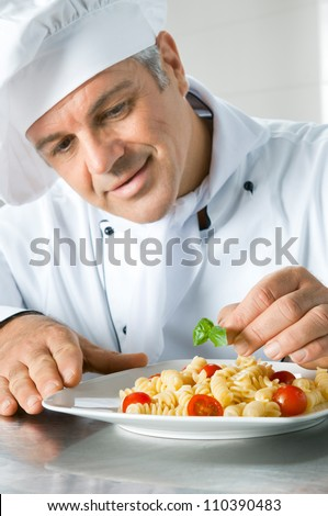 Happy smiling chef garnish an Italian pasta dish with basil leaves