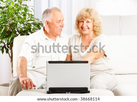 Happy smiling elderly couple working with laptop at home