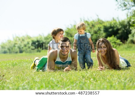 Happy smiling family of four lying on grass in sunny summer park