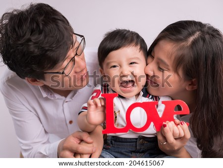 "Happy Smiling Family Portrait isolated on White Background. Baby boy holding ""LOVE"" symbol"