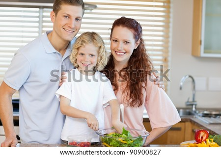 Happy smiling family preparing salad together