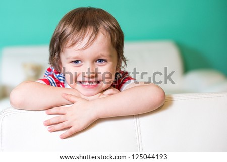 Happy smiling little child boy sitting on a sofa in living room