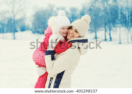 Happy smiling mother and child together in winter day