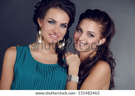 Happy smiling two women on gray background