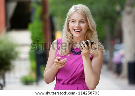Happy smiling woman talking on cell phone outdoors in city