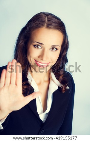 Happy smiling young business woman showing stop gesture
