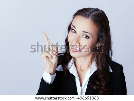 Happy smiling young businesswoman showing blank area for sign or copyspase, over grey background. Brunette woman in business concept studio shoot.