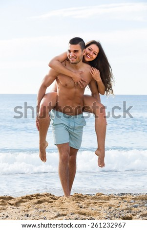 Happy smiling young lovers couple spending time together at sea shore