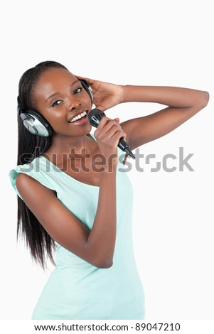 Happy smiling young woman singing against a white background