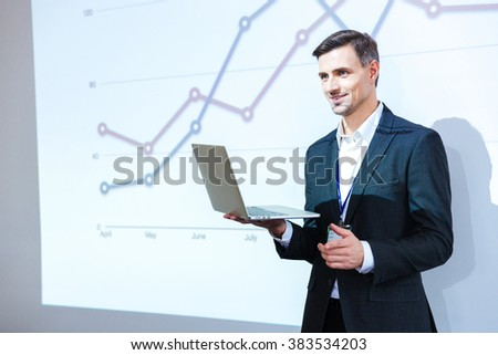 Happy speaker holding laptop and giving presentation in conference hall