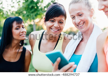 Happy sports women looking at fitness result on mobile phone