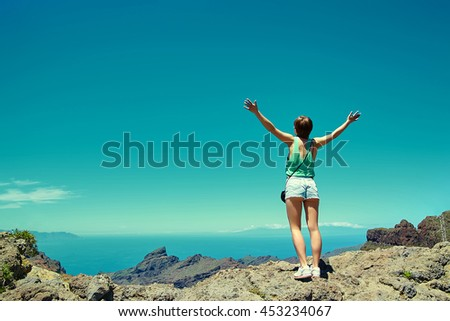 Happy stylish girl woman in casual hipster clothes standing on the cliff of mountain with raised hands to the sun and celebrating success