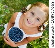 Happy summer - Lovely girl with fresh blueberries in the garden - stock photo