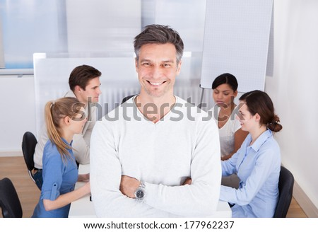 Happy Team Leader With Arm Crossed Standing In Front Colleagues Sitting At Table