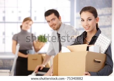 Happy team of businesspeople moving office, packing boxes, smiling.?