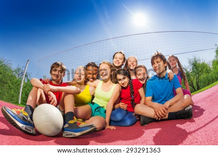 Happy teenagers who sit on volleyball game court